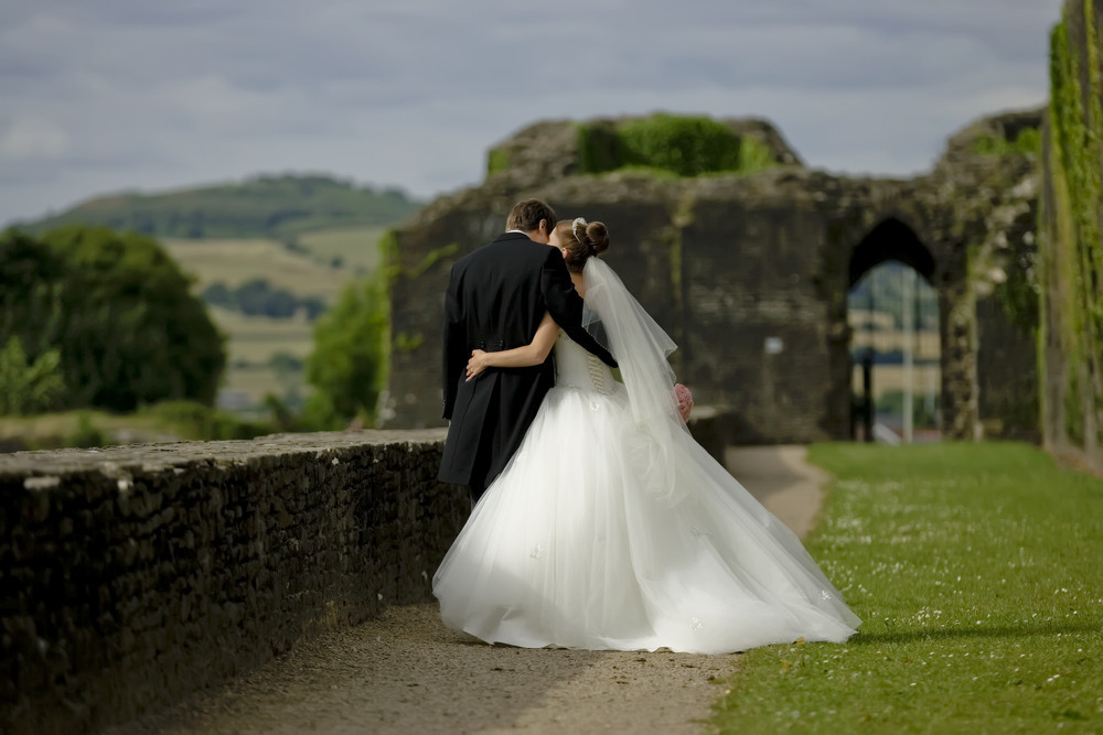 Bride and Groom taking a  walk at Caerphilly Castle - Wedding Photography at Caerphilly Castle