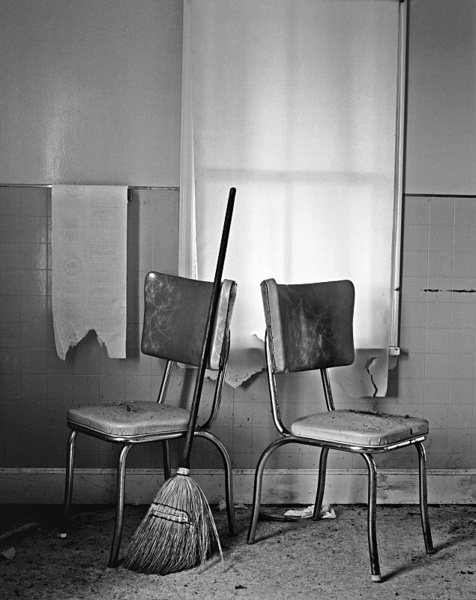 Interior with two chairs and sweeping brush. - Abandoned America