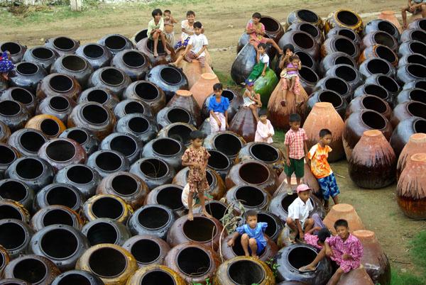 Children sitting on earthenware pots - Burma