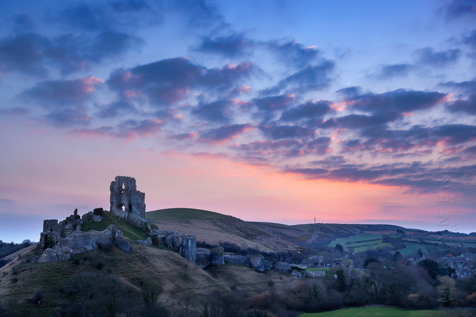 Warm glow of dawn lights up the sky behind Corfe Castle
