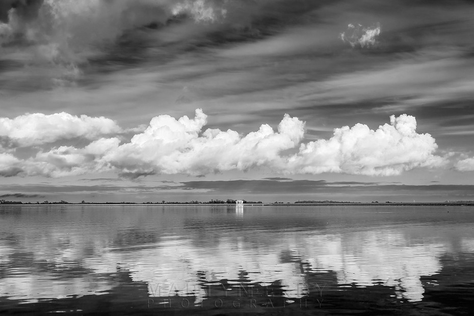 Fluffy clouds reflect in the reservoir at Grafham Water