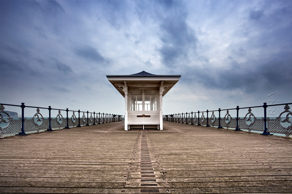 Swanage pier shelter under an atmospheric sky