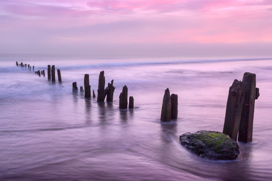 Beautiful image of beach groynes at sunrise in North Yorkshire