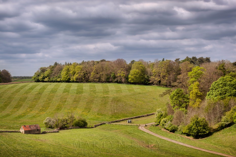 Hatherop Estate in the afternoon sunshine under stormy clouds