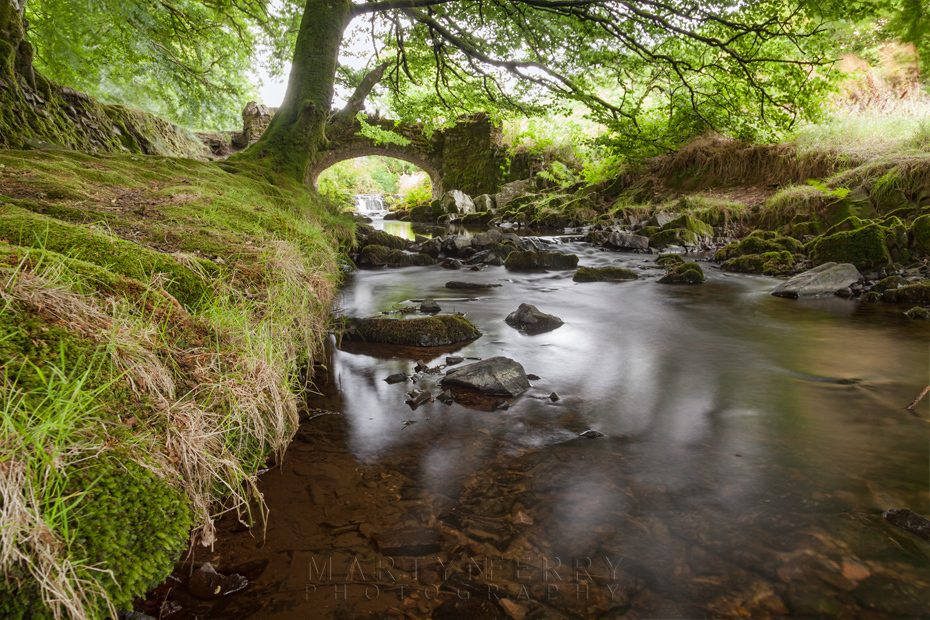 Robbers Bridge in Exmoor under the shady canopy of trees