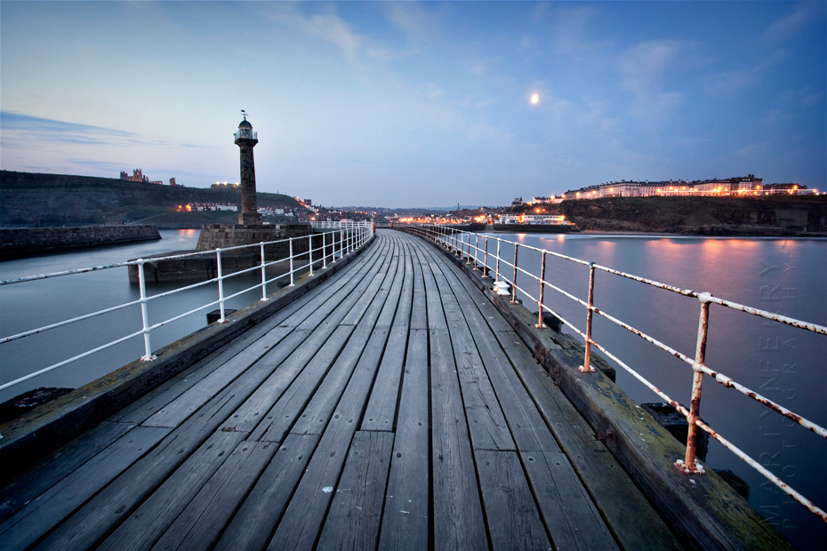 A view along Whitby pier to the lights of the town under an early morning moon