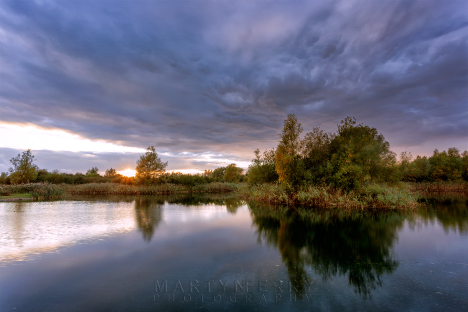 Storm clouds over a lake at Ouse Fen