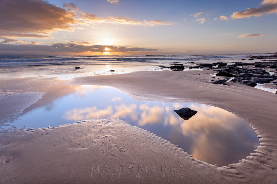Beach pool reflection of the sunset clouds at Dunraven Bay