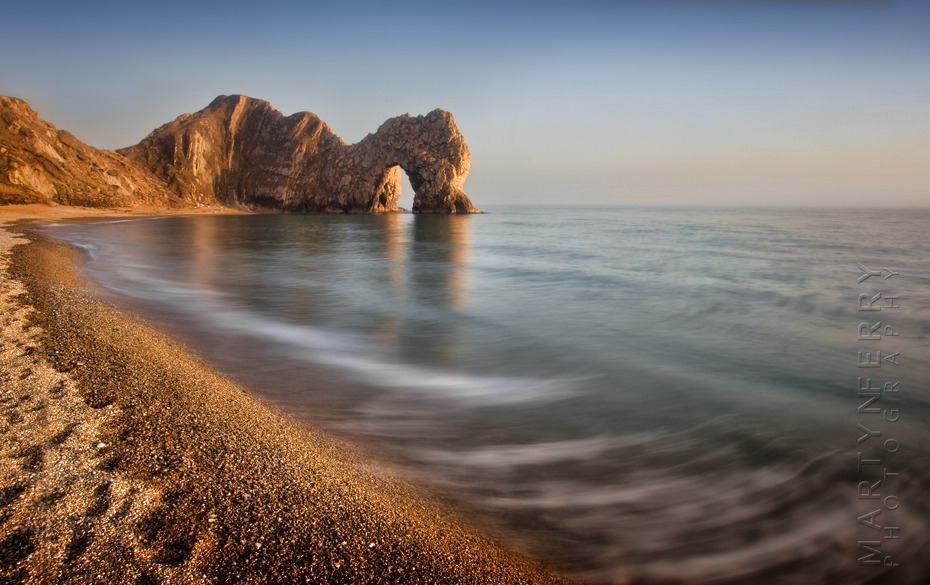 Classic sunset image of Durdle Door with long exposure