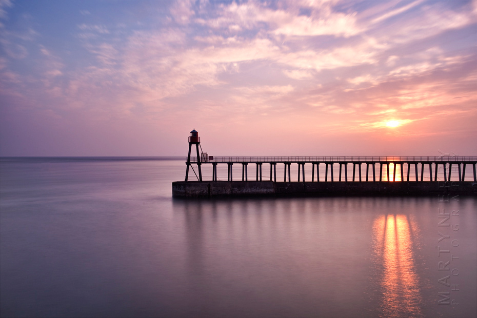 Vibrant sunrise reflection through Whitby pier