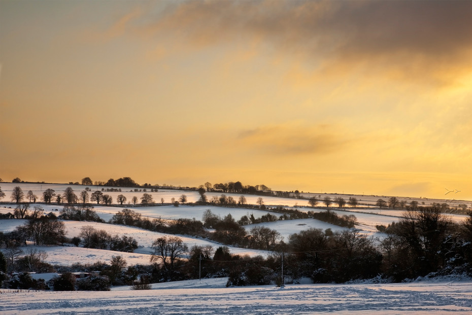 Stunning landscape view of a snowy Cotswold scene at sunset