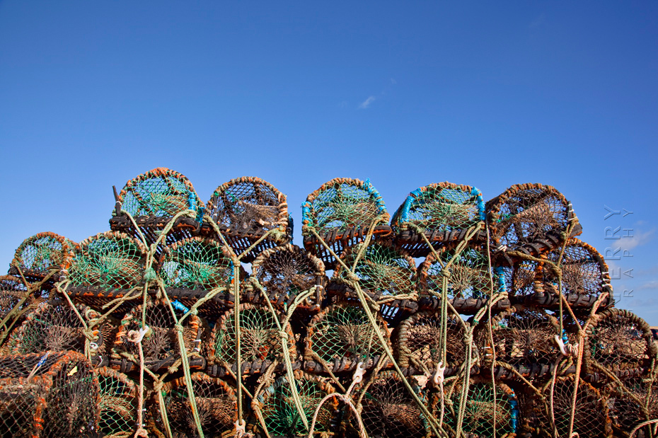 Stack of crab pots at Seahouses harbour under a clear blue sky
