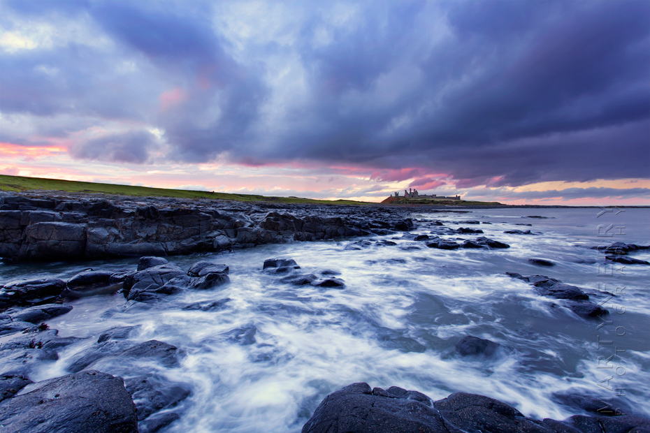Stormy clouds at sunset over Dunstanbrugh Castle in Northumberland