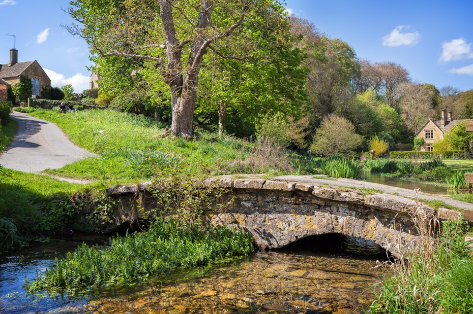 Ancient stone bridge at Upper Slaughter in the Cotswolds