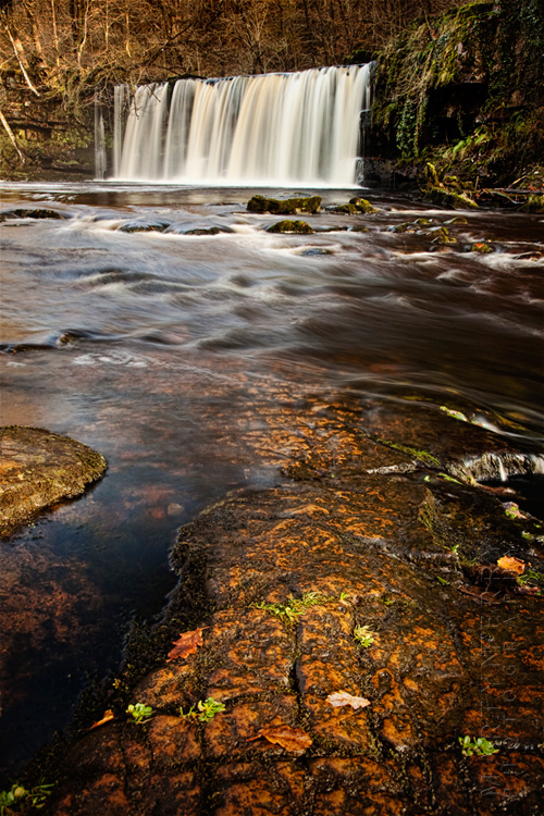 Autumn image of Welsh waterfall and river rocks