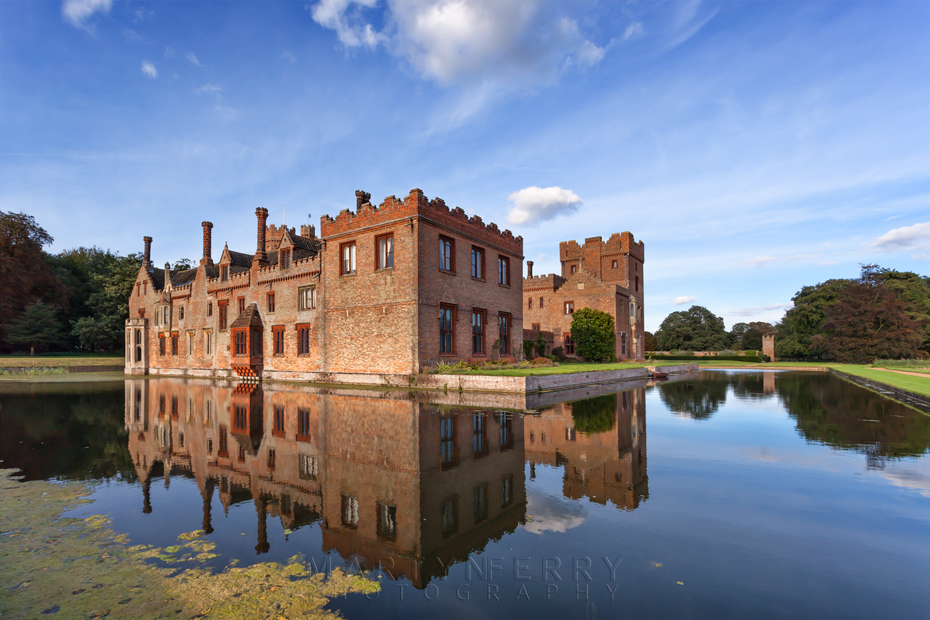 Oxburgh Hall bathed in evening sunlight is reflected in the moat