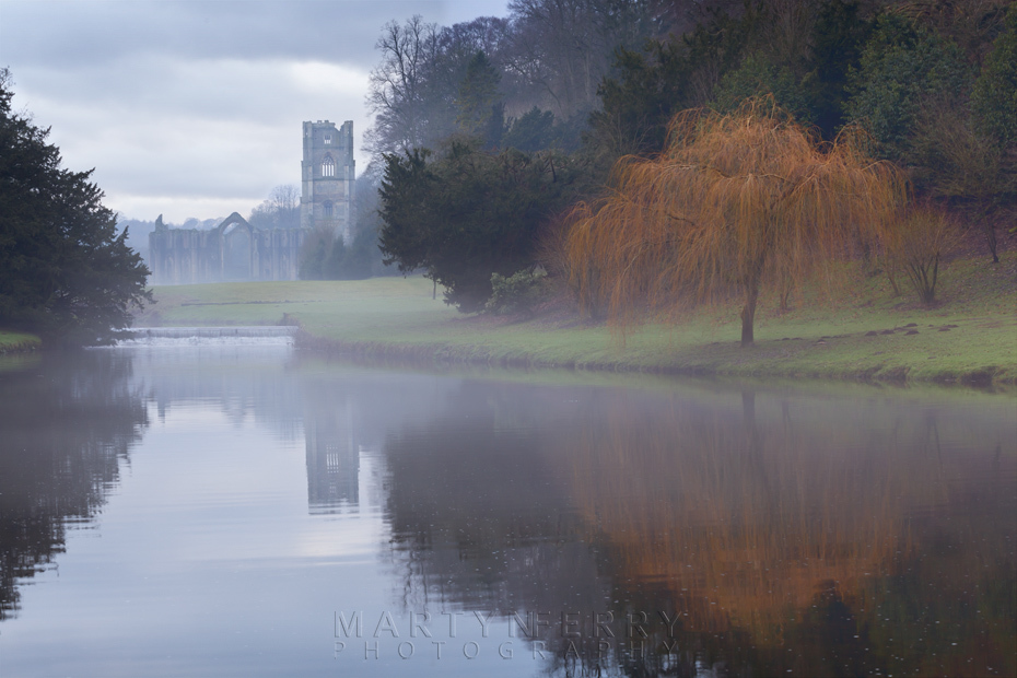 Mist over the lake with Fountains Abbey in the distance