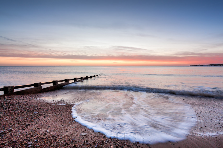 Waves spread over Swanage beach in Dorset at sunrise