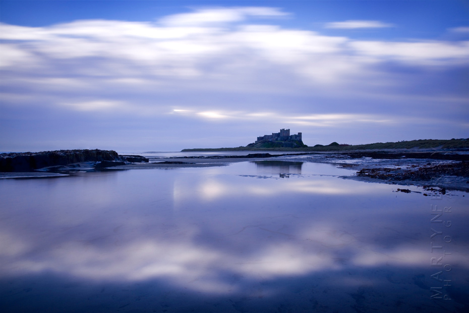 Clouds reflect in the landscape around the magnificent Bamburgh Castle at sunrise