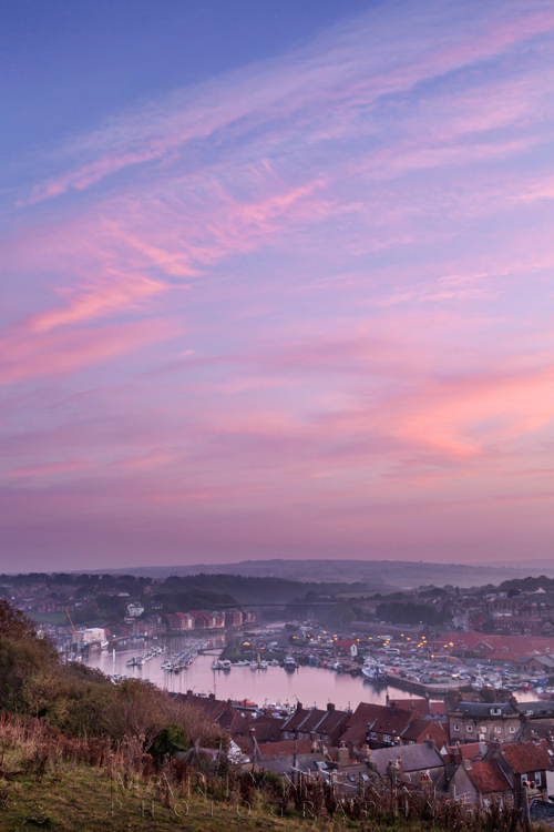 Striking sunset image of Whitby town under sunset clouds