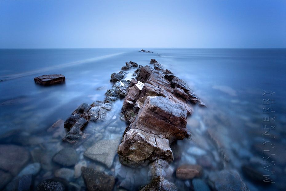 Spectacular cool blue image of Peveril Point rocks