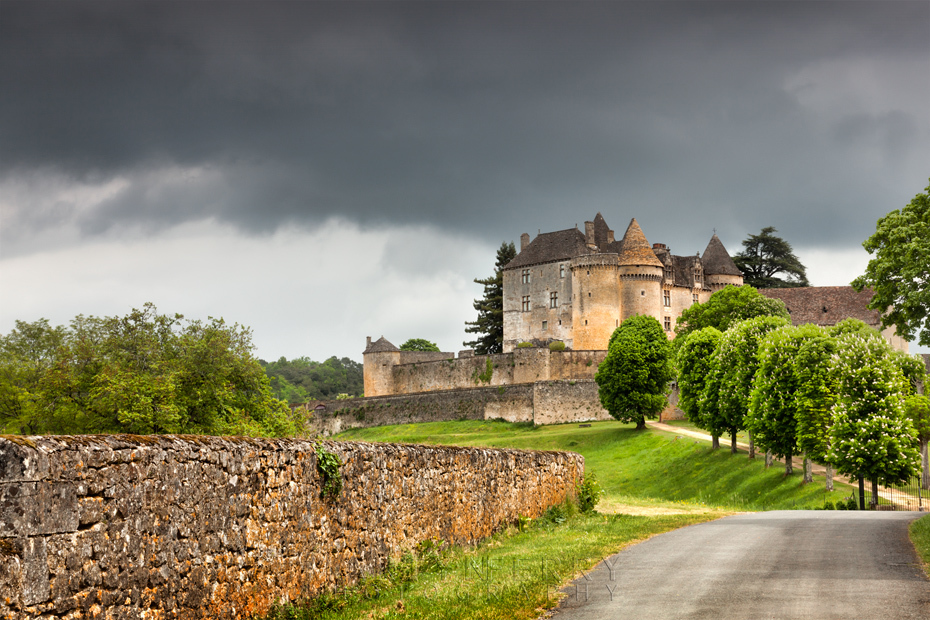 Impressive Chateau de Fenelon under storm clouds and sunlight in the Dordogne