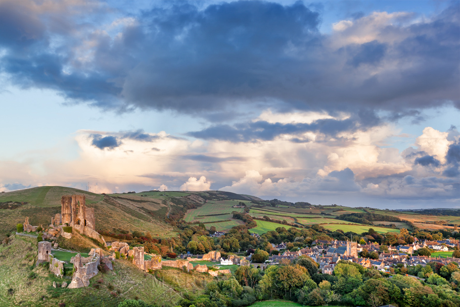 Sunset light over Corfe Castle ruins and village in Dorset