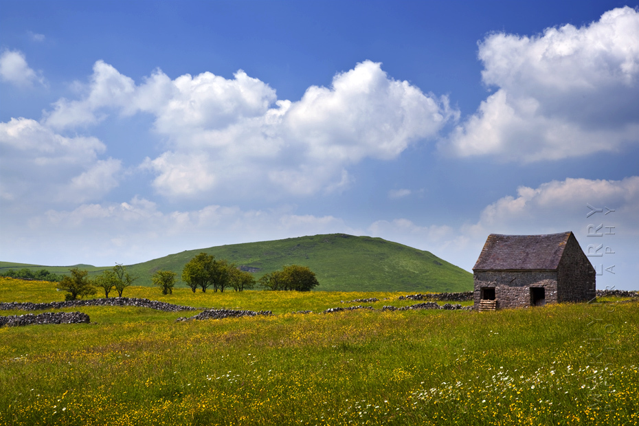 Beautiful Peak District image of barn and summer clouds.