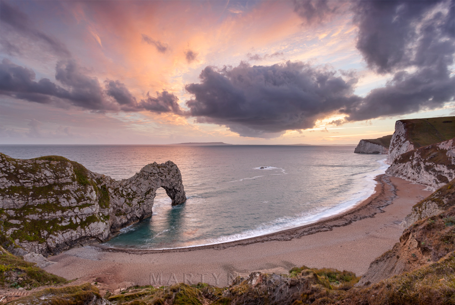 Sunset colours the clouds over Durdle Door