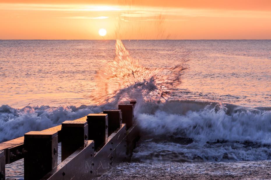 Splashing waves lit by the sunrise light on Swanage beach
