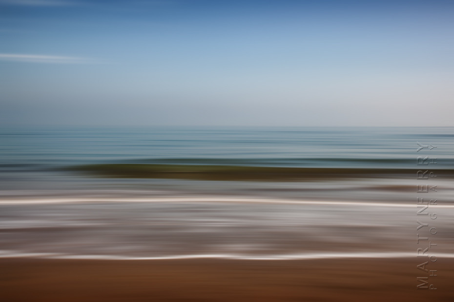 Beautiful minimal photograph of beach waves and sky in Dorset