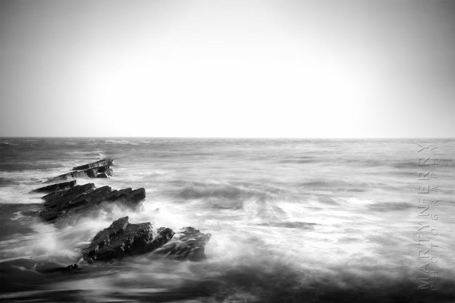Black and white photograph of waves crashing off the Dorset coast