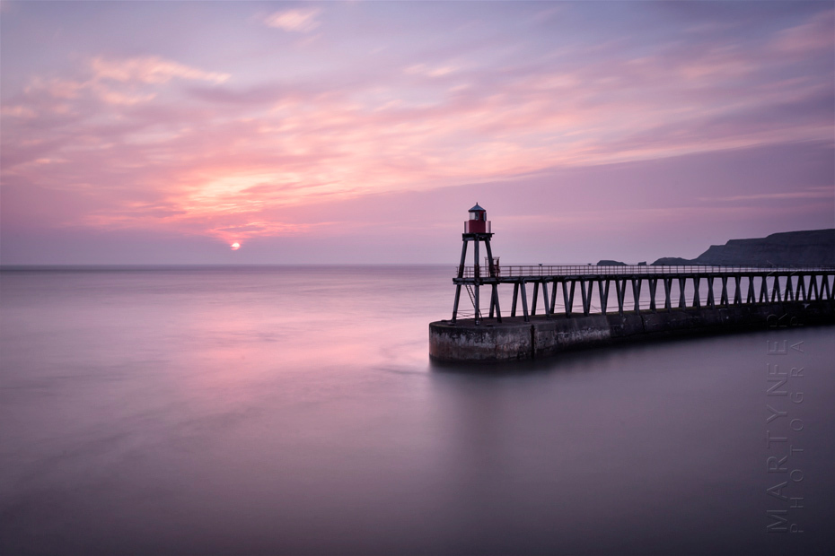 Colourful sunrise image of Whitby pier in North Yorkshire