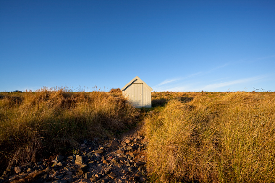Morning sunshine at Bamburgh on a solitary beach hut