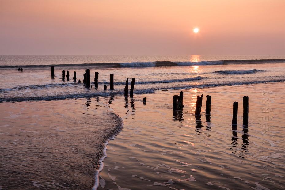 Sandsend groynes at sunrise in warm orange light