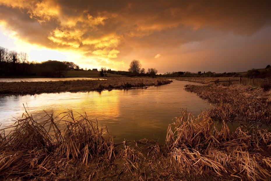 Image of warm sunset of a stormy evening over cotswolds river
