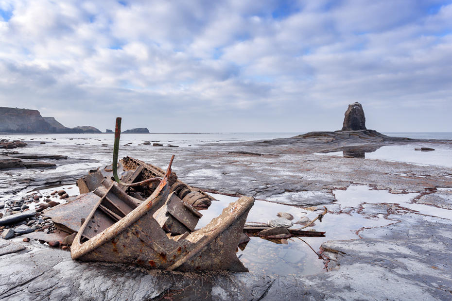 Saltwick Bay shipwreck with Black Nab under fluffy clouds