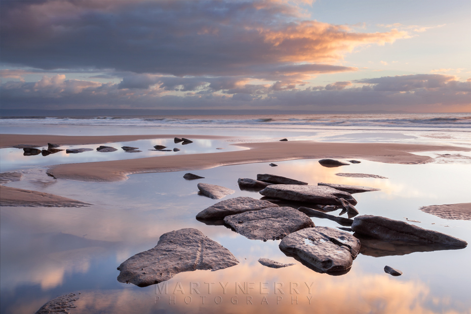 Rock pools reflect the setting sun at Dunraven Bay in Wales