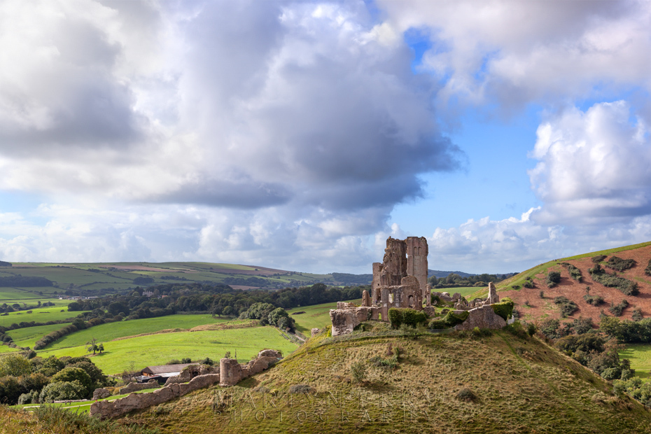 Corfe Castle in the morning sun under fluffy clouds