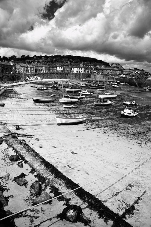 Striking black and white image of Mousehole harbour