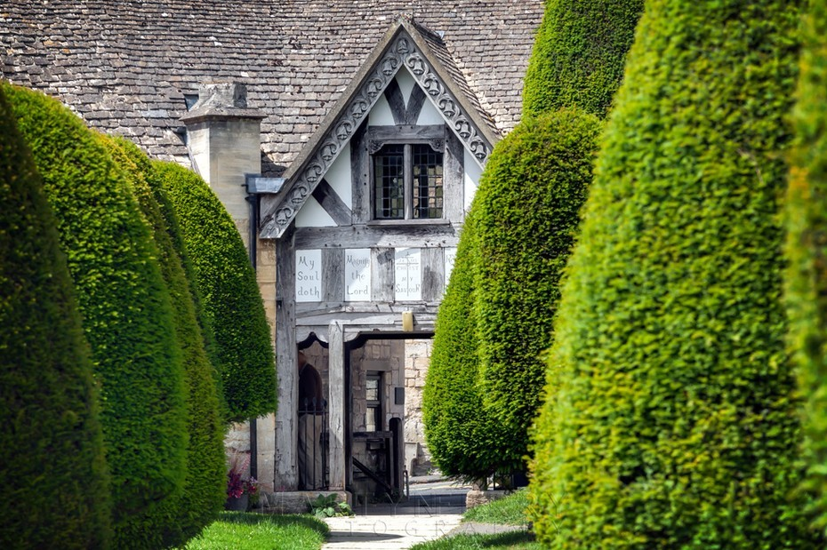 Green yew trees in front of the Lych Gate in Painswick