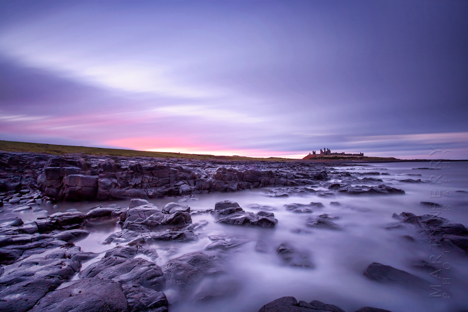 Sunset colours over Dunstanbrugh Castle in Northumberland