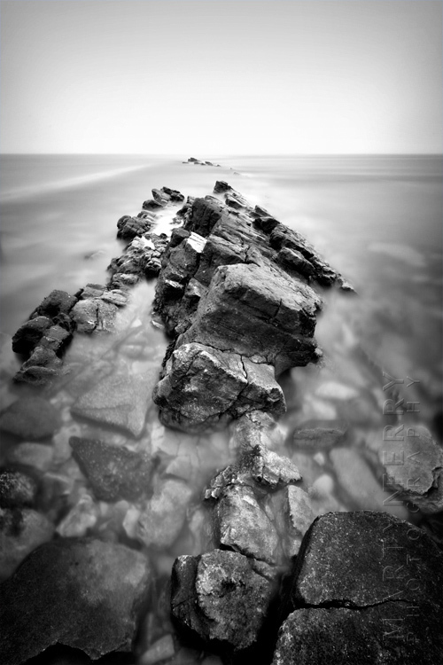 Beautiful black and white image of dramatic rocks in a smooth ocean