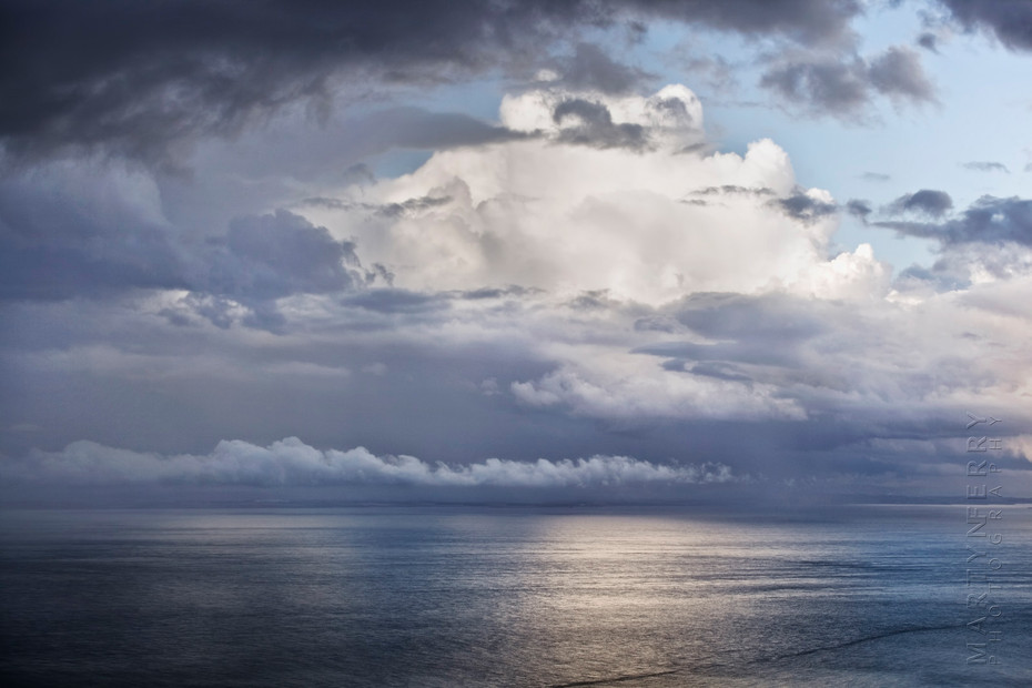 Photo of huge clouds over a calm ocean