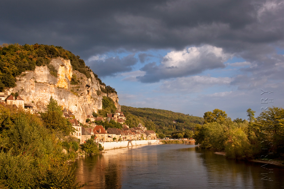 Warm sunshine on La Roque Gageac with stormy clouds above