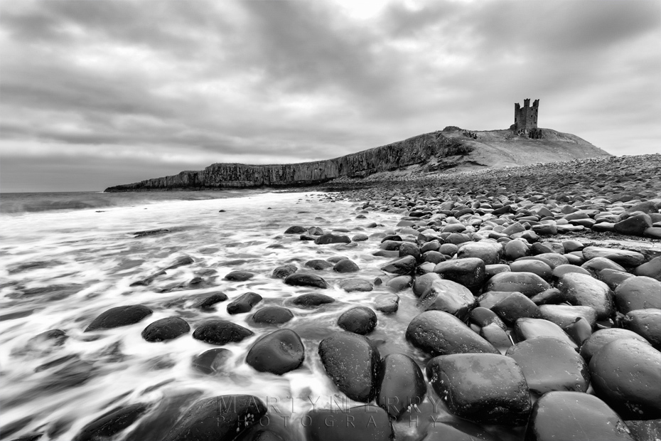 Dunstanburgh Castle under stormy clouds