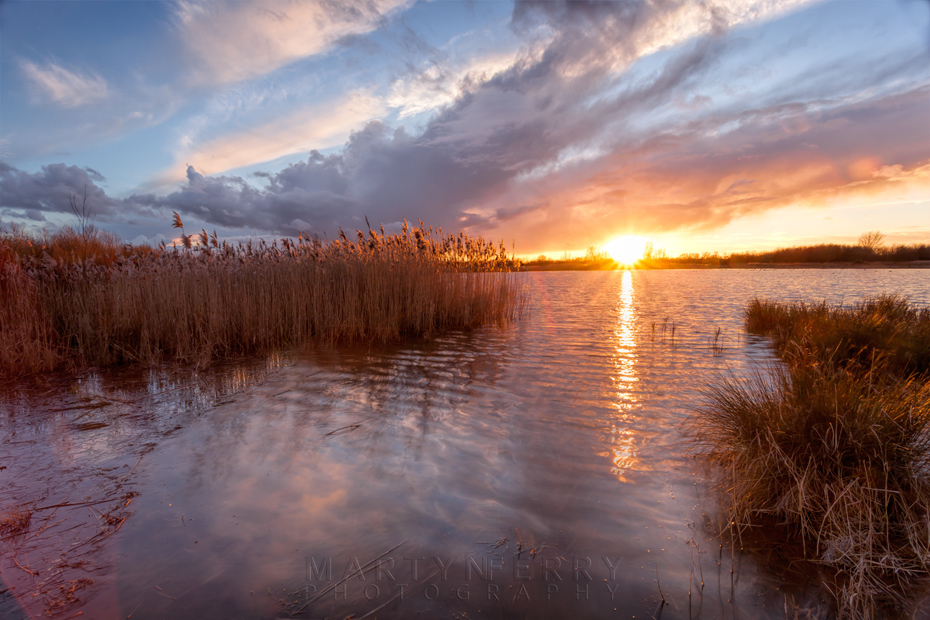 Bright sunset beams beneath the clouds at Ouse Fen Nature Reserve