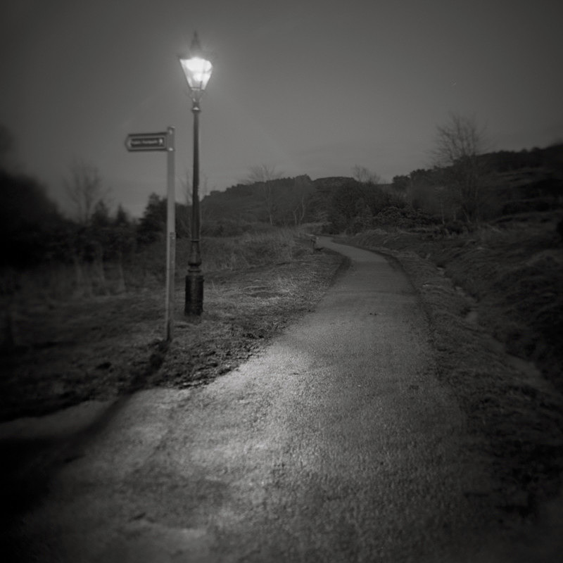 Black and white Photograpth of The Tarn Path approach Ilkley at night in street lighting