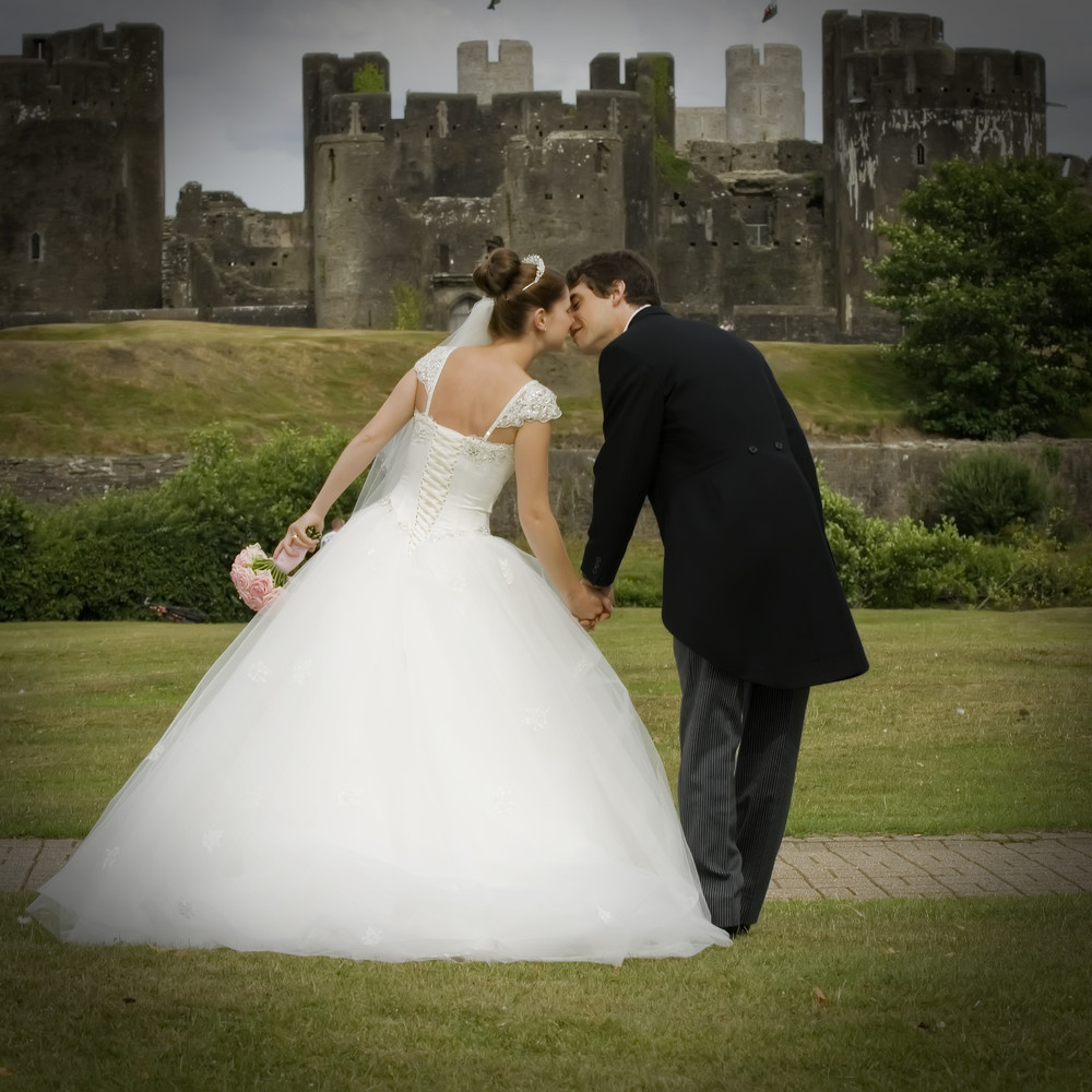 Bride and groom kissing at Caerphilly Castle - Wedding Photography at Caerphilly Castle