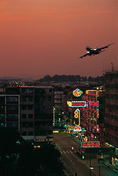 KM-172 Plane flying into Kai Tak over Kowloon city at dusk - 1985